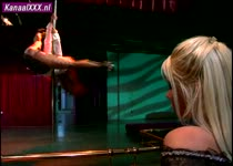 Lesbische paaldanseres geeft het nieuwe meisje een sexy showtje.