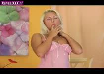 De mooie blondine bevredigt zichzelf met een grote roze dildo
