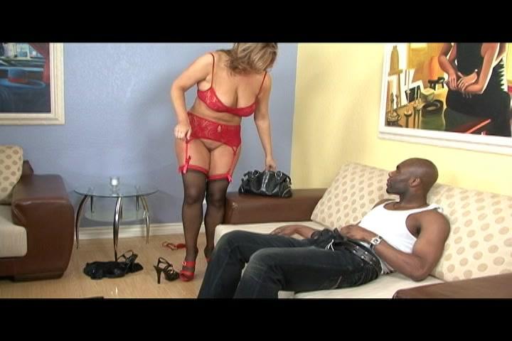 De geile milf in sexy lingerie trekt zijn broek uit