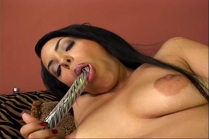 Met haar mond maakt ze de glazen dildo nat en masturbeert haar kale kut
